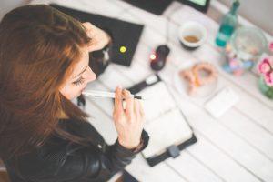 Frau am Tisch sitzen, denkt über berufliche Neuorientierung nach.